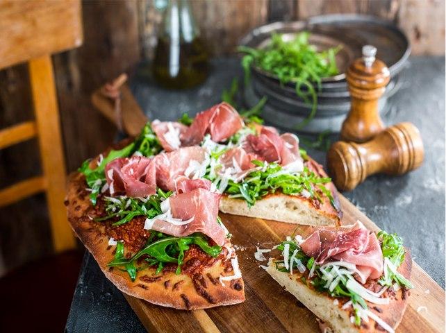 Pizza de jamón, parmesano y rúcula