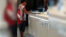 Niño hace la tarea de clase en una tablet de un centro comercial
