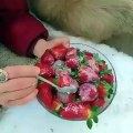 Un ours qui mange des fraises préparées par une femme