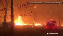 Firefighters drive down road surrounded by wildfire