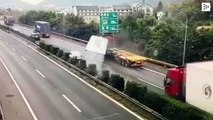 A lucky driver escapes from being crushed by a container that falls from a truck