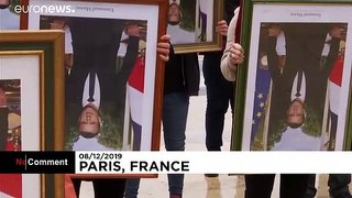 French climate activists hold stolen Macron portraits at protest