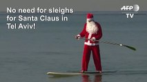 Santa Claus floats to Tel Aviv on his standup paddleboard