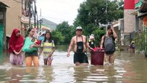 Indonesia: residents wade through flood water