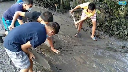 Citizens are using shovels and other improvised tools to clear the mud on the road