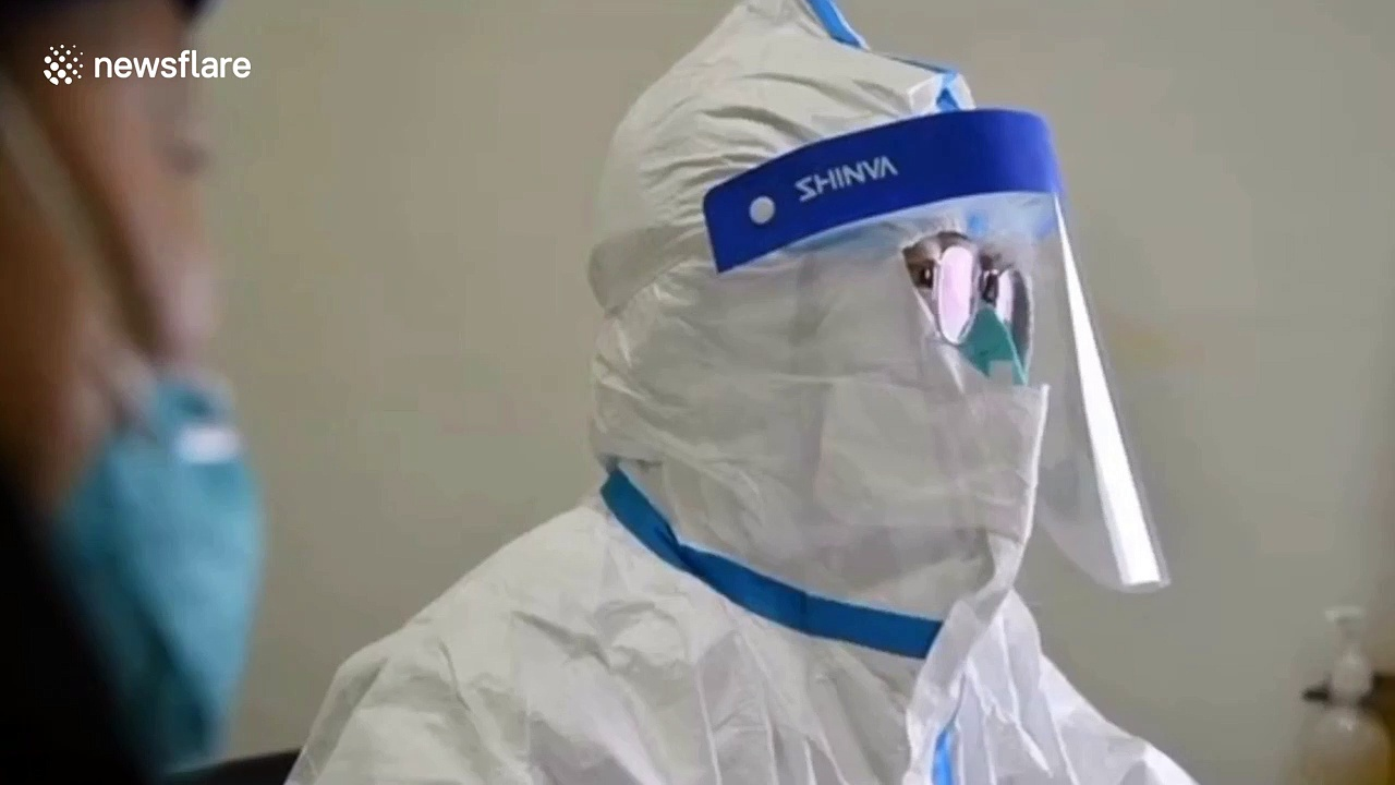 Doctors in protective clothing treat patients in Wuhan hospital during the coronavirus outbreak