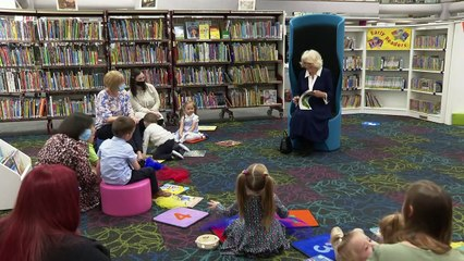 Camilla reads to small children during library visit