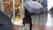London shoppers struggle with umbrellas during Storm Dennis wind and rain