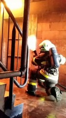 Deux pompiers forment un bouclier d'eau pour se protéger contre des flammes