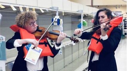 Violisten spelen serenade bij rekken zonder wc-papier met lied van zinkende Titanic