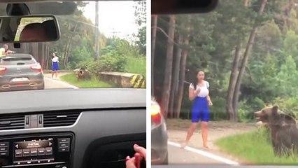 Elle sort de sa voiture pour aller prendre une photo avec un ours