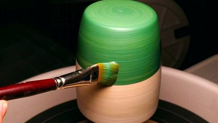 Ceramist evenly paints designs onto spinning pottery