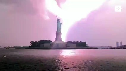 An impressive electric lightning strikes next to the Statue of Liberty