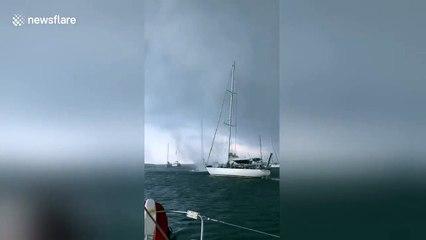 Une trombe marine passe entre 2 bateaux en mer