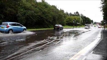 Motorists drive through flood water on Scot Lane, Wigan