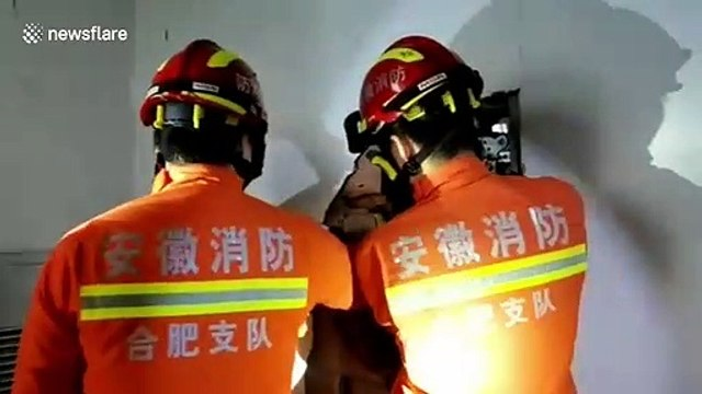 Chinese firefighters tear down wall to free people trapped in lift
