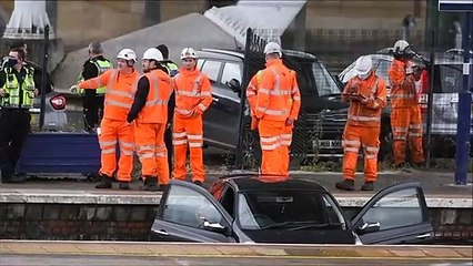 Workers remove a car from the tracks at Stirling Railway Station