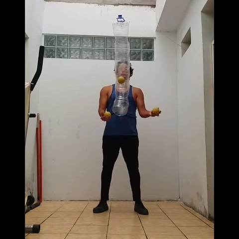 Guy Ties a Plastic Pipe Against His Chest and Performs Juggling Tricks With Balls