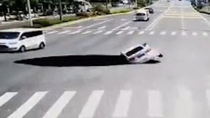 Coche cae en un sumidero gigante en una carretera en China