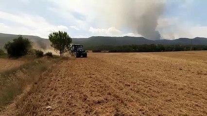 Els pagesos llauren els camps per fer de tallafoc en el cas que l'incendi hi arribi